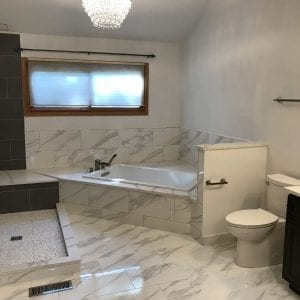 Master bathroom remodeling in Hoffman Estates - granite floor tile and tiles, black and white new shower and tub
