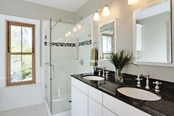 Bright white remodeled bathroom. Glass shower and granite counters.