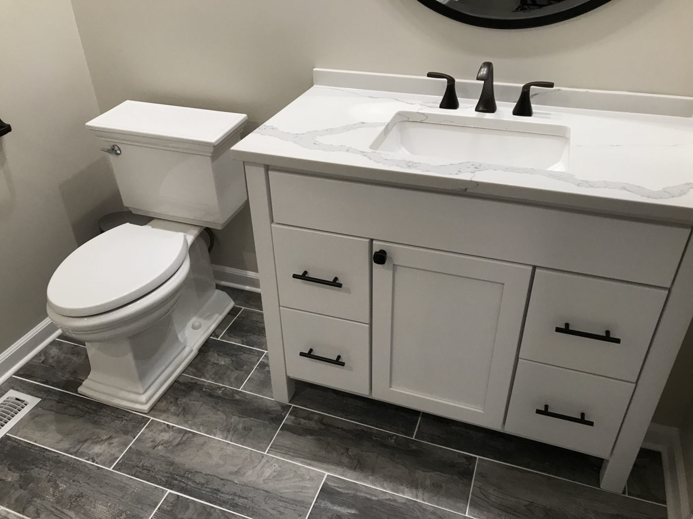 Bathroom Remodeling in Hinsdale - new flooring white and black cabinets and sink